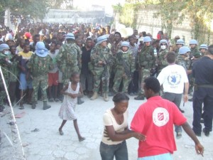 Assisted by military forces, Salvation Army staff and volunteers prepare to distribute meal rations to a crowd in Port au Prince, Haiti.