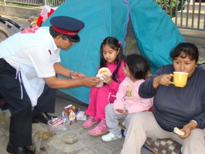 A Salvation Army officer provides a warm meal to a displaced family in Chile.