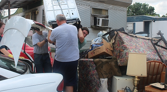 Volunteers remove damaged items from flooded homes in Madison, Indiana