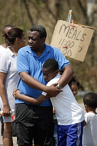 Jeremy Govan and his son wait for meals for victims of hurricane Katrina. Govan lost his home in the storm. (Photo by Ron Londen / Journey Group)