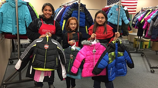 Young girls volunteer at the new Coats for Kids event (and get to choose a coat to take home, too!).