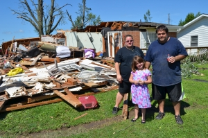 The Martinez family stands in front of what remains of their Kokomo home
